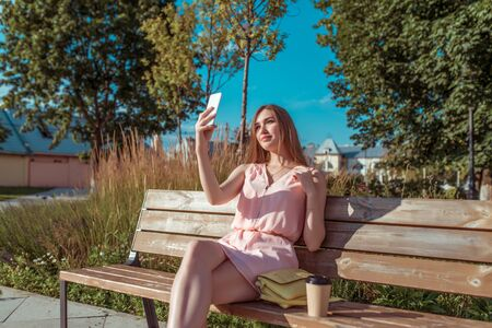 beautiful girl pink dress, takes pictures phone, summer city park sits bench, cup coffee tea, reads writes message Internet, online application social networks. Happy smiling, free space for text