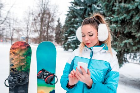 Beautiful happy girl, winter outdoors, background trees Christmas trees snow. Snowboard riding board. In hands mobile phone, writes reads message. Resting winter resort weekend. Free open copy space Stock Photo