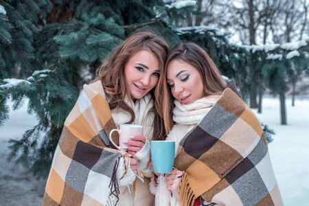 Two girls girlfriends women, winter on the street forest park warm themselves covered with warm blanket, hands mug with hot drink coffee tea. Weekend stay resort. Background snow drifts trees spruce