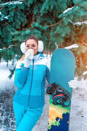 girl in winter drinks from cup hot drink coffee tea, warms up on cold winter day resort on weekend. Snowboard for skiing, warm sports overalls for fitness in nature