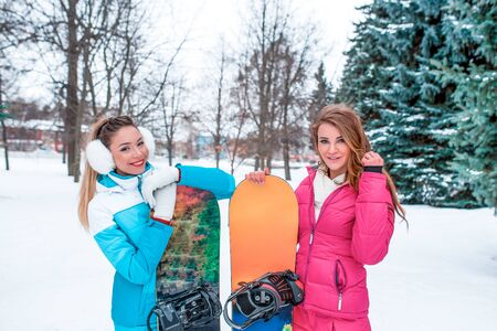 Two girls girlfriends women, happy smiling, winter outdoors park, background snow drifts. Boards skating, snowboards, having fun, laughing. Resting winter resort weekend. Free open copy space