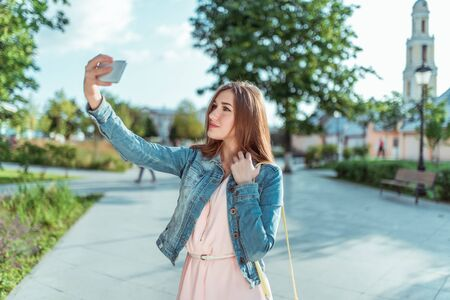 Beautiful girl in pink dress jeans happy smiling her mobile phone, taking pictures herself selfie standing in summer city park emotions comfort and pleasure. Video call application online Internet