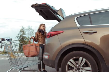woman in summer autumn in car parking lot, open trunk, takes out puts bag purchases shopping center, trolley from store, close-up crossover machine. Leather jacket and bag