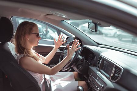 Girl driving car in cabin. Hand gesture accident signal conflict, emotions stress aggression discontent. Pink dress summer in parking lot mall. Misunderstanding scandal and accident on road Stok Fotoğraf