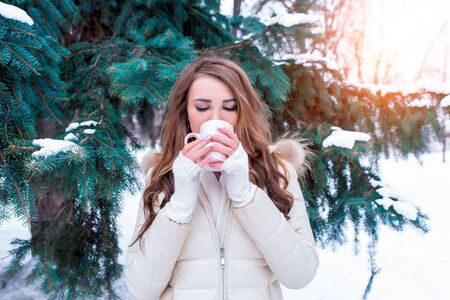 Girl in winter drinks a hot drink from a mug, weekend at resort, background green trees snowdrifts. In a warm jacket, cuffs and a scarf. Heated coffee tea in cold weather Stok Fotoğraf