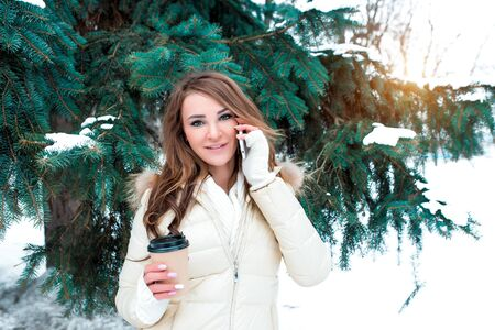 Girl in winter calls on phone, her hand cup with hot drink coffee tea, weekend resort, background green Christmas trees snowdrifts. In warm jacket, cuffs scarf. Listens voice message online Internet.