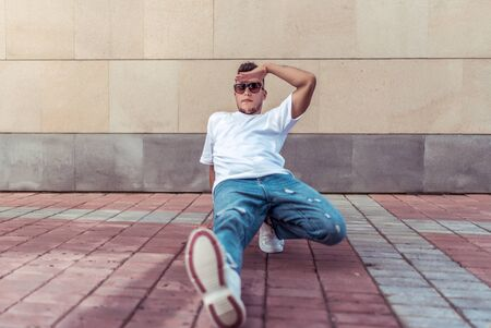 male athlete, sits down in distance, summer city, hip-hop style, breakdancer. Free space motivation text. Active youth lifestyle, modern fashionable hipster, street dancer. T-shirt jeans sunglasses
