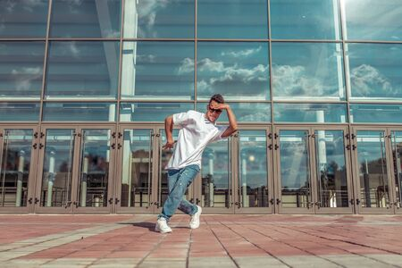 Male athlete dancing glass window background, summer city, hip hop style, breakdancer. Free space motivation text. Active youth lifestyle, modern fashionable hipster, street. T-shirt sunglasses.