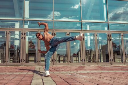 Male athlete, jumping dancing glass window background, summer city, hip hop style, breakdancer. Free space motivation text. Active youth lifestyle, modern fashionable hipster, street dancer. Jeans Stok Fotoğraf