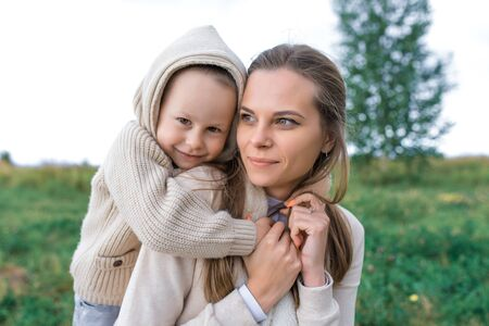 Happy family mom woman little boy weekend resting, laughing smiling having fun, playing. Hug, background green grass. Warm casual wear, hooded sweater. Caring support love nurturing tenderness