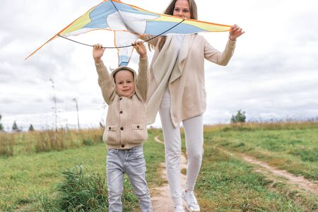 Little boy mom woman happy family, autumn day summer city park, launches kite airplane, laugh, smile, have fun, play. Warm casual wear sweater with hood. Caring support love parenting weekend nature Stok Fotoğraf