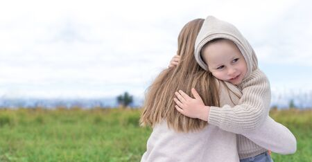 Happy family mom woman with little boy hugging at weekend. Hug, background green grass. Warm casual wear, hooded sweater. Caring support love and nurturing tenderness. Free space for text