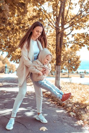 Happy family, mother woman little boy 4-5 years old, playing having fun, laughing park, background trees foliage. Warm casual wear, hooded sweater. Caring support love and nurture weekend nature