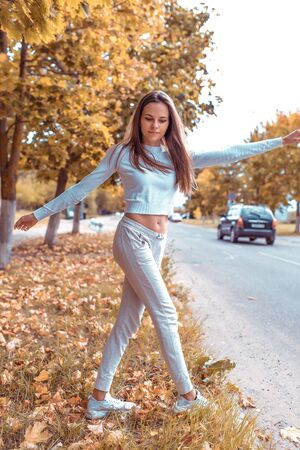 Beautiful girl in autumn on nature walks in grass, background trees fallen leaves, road car. Warm casual wear. Emotions of comfort of relaxation pleasure in nature. Long hair casual makeup Stok Fotoğraf