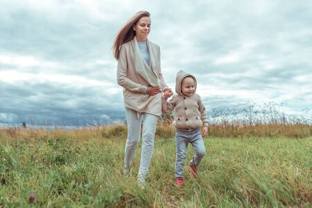 Happy family, mom woman with little boy 4-5 years old on weekend walk in park field, background green grass. Warm casual wear, hooded sweater. Caring support love and parenting hold hands Stok Fotoğraf