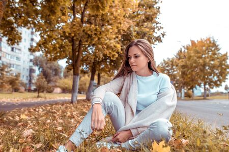 Beautiful girl in autumn on nature sits in grass, background trees fallen leaves, road. Warm casual wear. Emotions of comfort of relaxation and pleasure in nature
