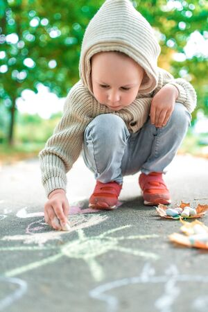 little boy child of 4-5 years old, autumn day in summer in city park, draws with crayons, he plays seriously and has fun. Warm casual wear sweater with hood. Caring love and parenting weekend nature