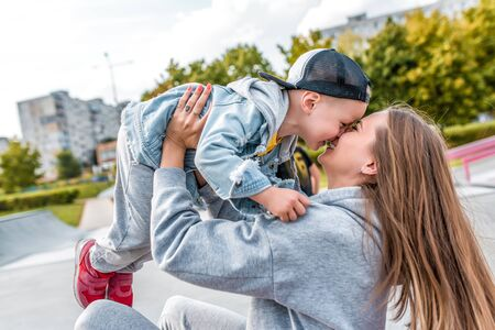 Young mother woman happy plays with little years old boy in city park, autumn clothes on nature, fun joy and emotions of tenderness of love and care. Laugh rejoice game Stok Fotoğraf