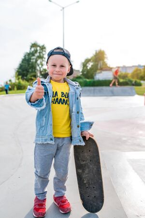 Happy little boy 3-5 years old, in summer on sports field in city, thumbs up, smiles, rejoices, parting words of instruction on skateboard. Autumn clothes. Emotions of pleasure and relaxation