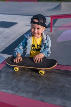 A happy little boy of 3-5 years old, in summer on sports field city, smiles at his joy, is learning hard to learn skateboarding. Autumn clothes. Emotions of pleasure and relaxation