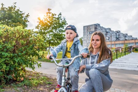 Young mother teaches woman to ride bicycle, plays with little boy 3-5 years old, in summer in city park, autumn clothes on nature, emotions of tenderness of love and care Stok Fotoğraf
