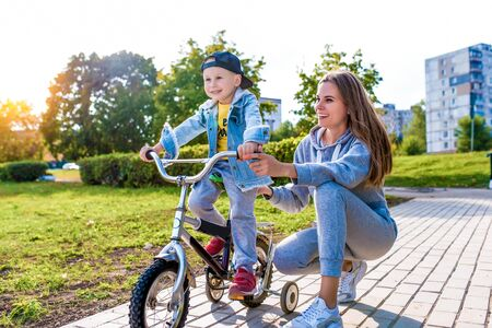 young mother teaches woman ride bicycle, plays with little boy 3-5 years old, happy laugh enjoy smiling, summer in city park, autumn clothes nature, emotions tenderness of love and care Stok Fotoğraf