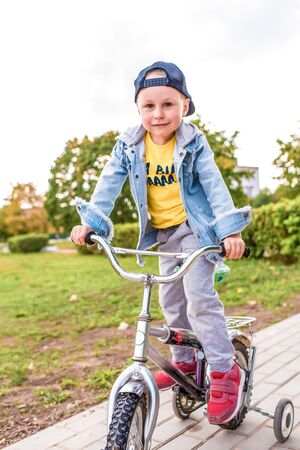 happy little boy of 3-5 years old, in summer in city park, smiles rejoices, is learning to ride a bicycle, learns how Autumn clothes. Emotions of pleasure and relaxation Stok Fotoğraf