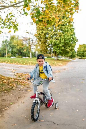 happy little boy of 3-5 years old, on road in summer in city, smiles his joy, learns to ride bicycle, learns how to learn. Autumn clothes. Emotions of pleasure and relaxation