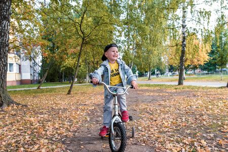 Happy little boy 3-5 years old, in summer in city park, smiles, rejoices, is working hard to ride bicycle. Autumn clothes. Emotions of pleasure and relaxation. Laughs and has fun Stok Fotoğraf
