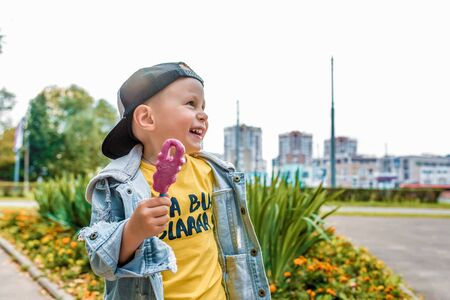 Happy little boy 3-5 years old, in summer in city park, smiles, rejoices, eats ice cream on stick. Autumn clothes. Emotions of pleasure and relaxation. Laughs has fun. Free space for copy text