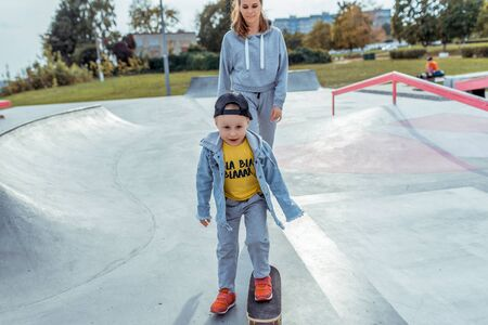 Young mother with little boy son, happy family learns to ride skateboard, summer outdoors, autumn day. Emotions of delight, joy of playground fun. Caring support assistance in training, parenting