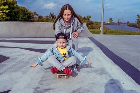 Young mother with little boy son, playground family learns ride skateboard, summer outdoors, autumn day. Emotions of delight, joy of happiness fun. Caring support assistance in training, parenting