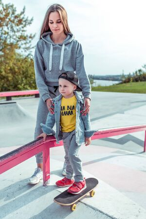 Young mother teaches to ride a skateboard, son of little boy, summer day. Autumnal clothes, casual clothes. Help and support in parenting. Caring for children. Stok Fotoğraf