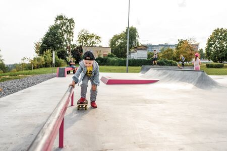 Little boy learns to ride a skateboard, in summer in the city on a sports field, autumn clothes. Free space for copy text.