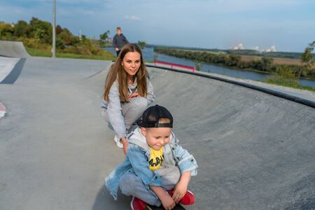 Young mother teaches ride skateboard, son of little boy, summer day. Autumnal clothes, casual clothes. Help and support parenting. Caring for children. Workout balance