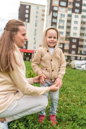 Young happy family, woman mom and little son boy. Hold each others hands, autumn is on street, smiling, walking and rejoicing. Casual warm clothes with hood jumper. Stock fotó