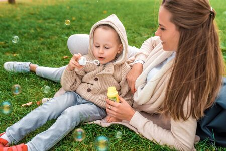 Happy family, young mother woman, little boy son 3-6 years old, emotions delight joy positive. Blow air bubbles, play relax on weekend warm casual wear, beige sweater with hood Stok Fotoğraf