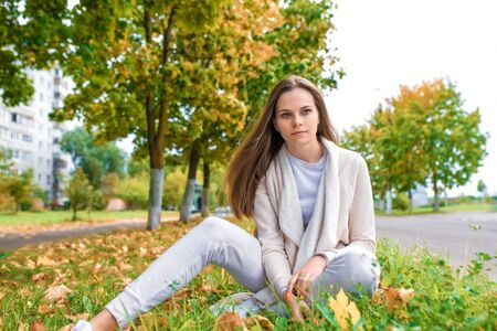 Beautiful woman in autumn sits in leaves, resting and dreaming and fantasizing, warm casual clothes, long hair, background trees road