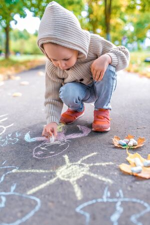 Little boy in autumn on street, draws on pavement, multicolored crayons. Warm clothes on a cold day, beige cardigan with a hood. Weekend breaks, creativity and drawings