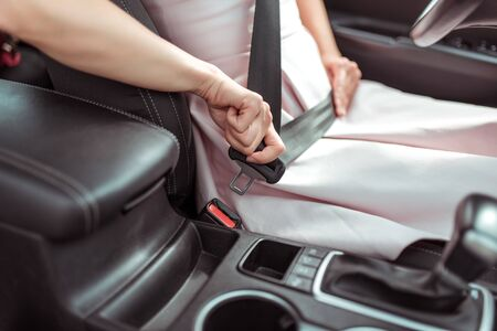 Close-up, woman driving car fastens her seat belt, automatic transmission, pink dress, in summer in city parking lot, traffic safety, activation of airbags in an accident