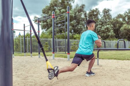 Athletic man exercises with straps loops  , lunges workout leg muscles, workout in summer in city, active lifestyle, modern fitness workout. Free space for motivation text