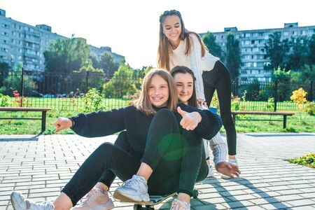 Three girls schoolgirls 13-15 years old, autumn summer day city, ride skateboard, happy smiling laughing, casual clothes, rest after school break. Emotions joy fun pleasure of teenagers Stok Fotoğraf