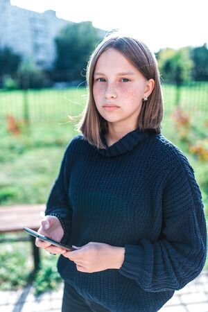 teenager girl 14-15 years old, in autumn day summer in city, holding smartphone, serious pensive, in casual clothes, sweater, outdoor portrait of teenager schoolgirl