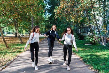 Three girls schoolgirls teenagers 13-15 years old, autumn summer day city, ride skateboard, happy smiling laughing, casual clothes, rest after school break. Emotions joy fun and enjoyment