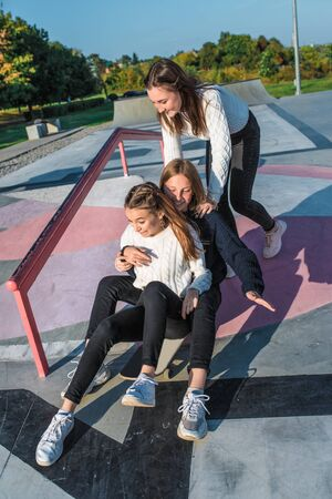 Three girls schoolgirls teenagers 13-15 years old, autumn day summer city, skateboarding. Emotions joy are fun enjoyment, happy are smiling laughing, casual clothes, relaxing after school on vacation