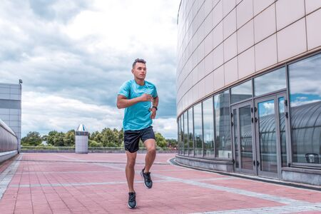 Athletic man running in jump in training, runner in sportswear, training in city during summer, active lifestyle, modern fitness workout. Free space for motivation text
