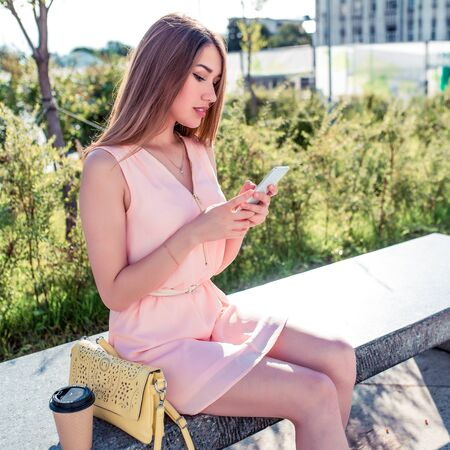 Beautiful girl pink dress, sits park bench, writes reads message mobile phone, application on Internet, social networks, summer city, fashionable modern fashion lifestyle. Handbag cup with coffee tea