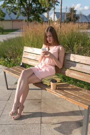 Beautiful girl pink dress, wooden bench, writes reads message mobile phone, application on Internet, social networks, summer city, fashionable modern fashion lifestyle. Handbag cup with coffee tea
