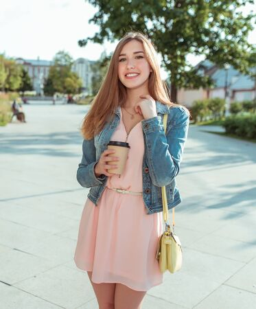 Beautiful girl in pink dress and jeans, happy smiling having fun and laughing, summer in city, fashionable and modern fashion lifestyle. A cup coffee with tea.