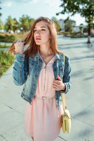 Beautiful girl student in pink dress and jeans straightens her hair, summer in the city, fashionable and modern fashion lifestyle. Yellow shoulder bag. Stok Fotoğraf